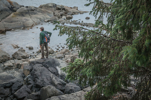 Troy assesses fish prospects at the edge of the sea in Sitka, Alaska (Clark James Mishler)