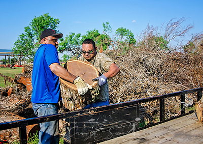 Refugio residents load mesquite logs onto a trailer, Sept. 30, 2017, in Refugio, Texas. Hurricane Harvey downed a large number of threes in the area, many of which are now cut up and waiting for curbside pickup. Some, like these men, are gathering the larger pieces for firewood and barbecues. (Photo by Carmen K. Sisson) (Carmen K. Sisson/Cloudybright)