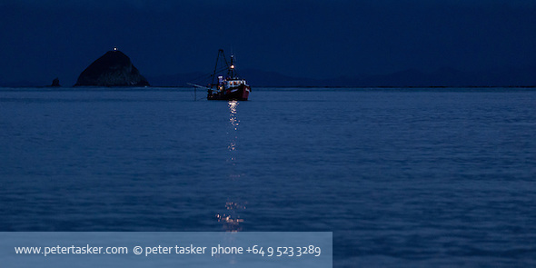 Night photograph of fishing trawler Corinthian preparing for an early morning departure from Port Jackson, Coromandel Peninsula, Hauraki Gulf, New Zealand. Channel Island in background and Great Barrier Island on the horizon. (Peter Tasker)
