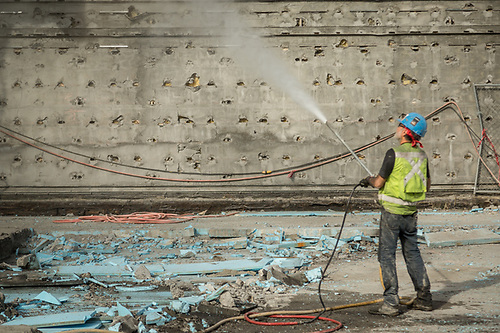 A construction worker waters down debris during a demolition project near the Moscone Center in San Francisco. (Clark James Mishler)