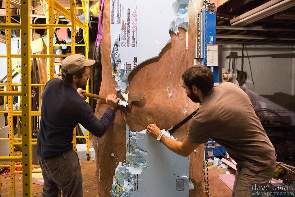 "Joel Erland (left) and Miguel Antonio Horn hack off the styrofoam mold on Horn's sculpture ""Colossus,"" a four meter statue of King Tutankhamen. (Dave Tavani)"