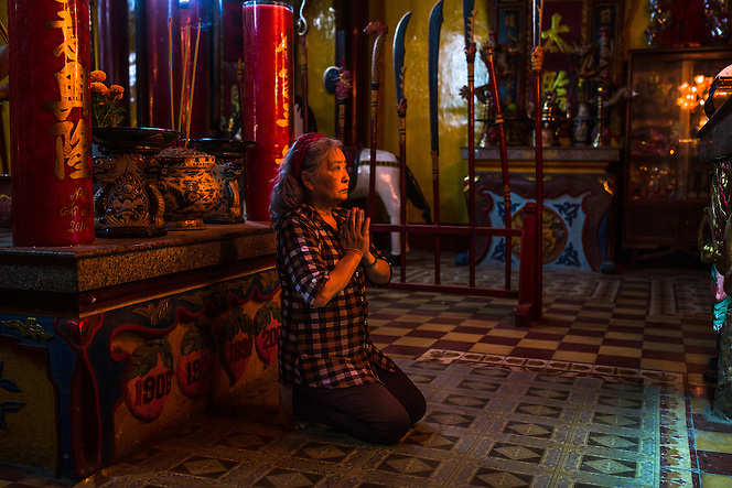Tran To Nga prays at a buddhist temple in Dong Nai, Vietnam, which stands in honor of one of her ancestors that founded the area. Just several weeks later, she would return to Paris to take on the monumental task of taking Monsanto chemical corporation to court over their production of Dioxin, better known as Agent Orange, which has destroyed, and still is affecting the lives of many Vietnamese, including Nga and her grown children still today. (Quinn Ryan Mattingly)