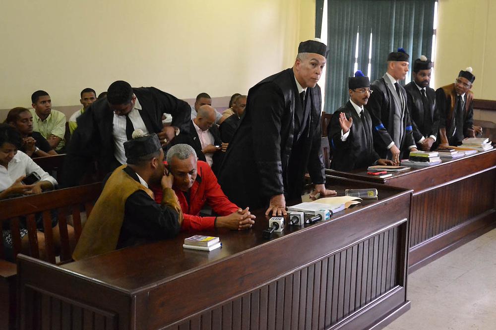Uno de los abogados habla al oído al acusado.