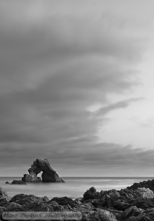 A vertical view of the arch rock offshore at Little Corona after sunset, in black and white using a long exposure to make the ocean water silky smooth.  I love the soft curves of the clouds drifting overhead. (Marc C. Perkins)