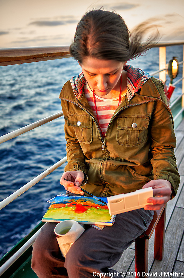 Grace working on a watercolor painting in the late afternoon sun. Aft deck of the MV World Odyssey crossing the Pacific Ocean. Semester at Sea, 2016 Spring Semester Voyage. Day 2 of 102. Image taken with a Leica T camera and 23 mm f/2 lens (ISO 100, 23 mm, f/2, 1/80 sec). (David J Mathre)