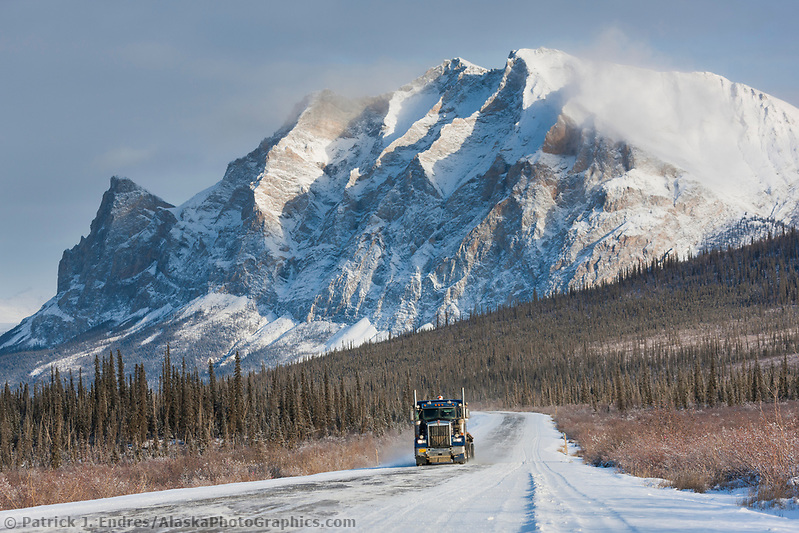 Semi tractor trailer travels the James Dalton Highway (the haul road) with mt Sukakpak rising in the distance. (Patrick J Endres / AlaskaPhotoGraphics.com)