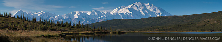 Sun rises on Mount McKinley and the Alaska Range as seen from Wonder Lake in Denali National Park and Preserve in Alaska. Mount McKinley also known as Denali is North America's tallest peak at 20,320 feet and towers over 18,000 feet above the surrounding lowlands. Other mountain peaks pictured include: Mount Brooks, Mount Silverthrone, Mount Tatum, and Mount Carpe. SPECIAL NOTE: This image is a panorama composite consisting of multiple overlapping images stitched together. (John L. Dengler)