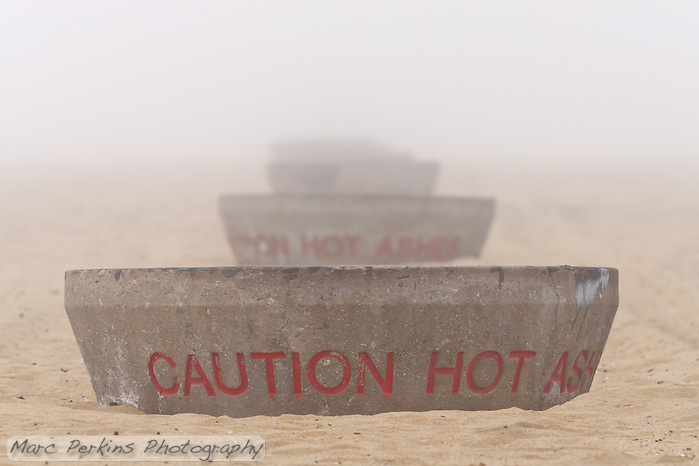 """A row of fire pits on the sandy beach appear as though they're a nesting set of matryoshka dolls (Russian nesting dolls).  Seen at Huntington State Beach in Huntington Beach, CA on a foggy New Year's eve.  They read """"Caution hot ashes"""" (Marc C. Perkins)"""