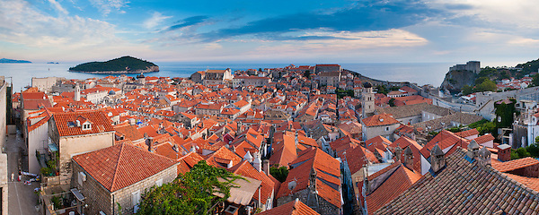 Panoramic photo of Dubrovnik Old Town from the city walls, Dubrovnik, Dalmatia, Croatia, Europe. This panoramic photo, taken from the city walls shows dramatic clouds over the red roofs of UNESCO World Heritage listed Dubrovnik Old Town, with Lokrum Island in the background. The Dubrovnik city walls are without a doubt the highlight of visiting this stunning old town on the Dalmatian Coast of Croatia, offering unrivalled views over cathedral spires, the Adriatic Sea and Lokrum Island.