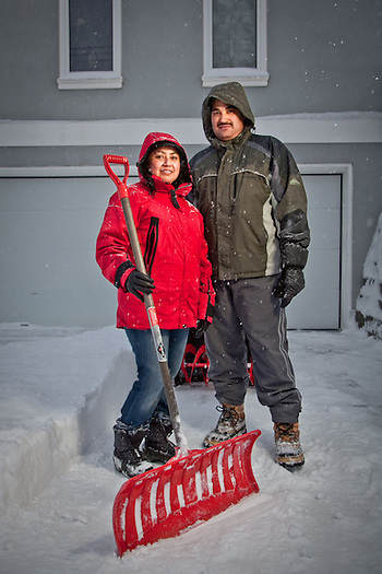 Lina Lagunes and Ermmelindo Cabos shovel snow at a home on 9th Avenue near P Street, Anchorage. (Clark James Mishler)