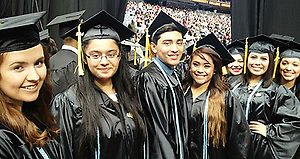 These East Early College High School students (black gown with blue cord) were some of the more than 100 seniors from that campus to receive their associate's degrees from Houston Community College SE two weeks before their high school diplomas. (Houston Independent School District)