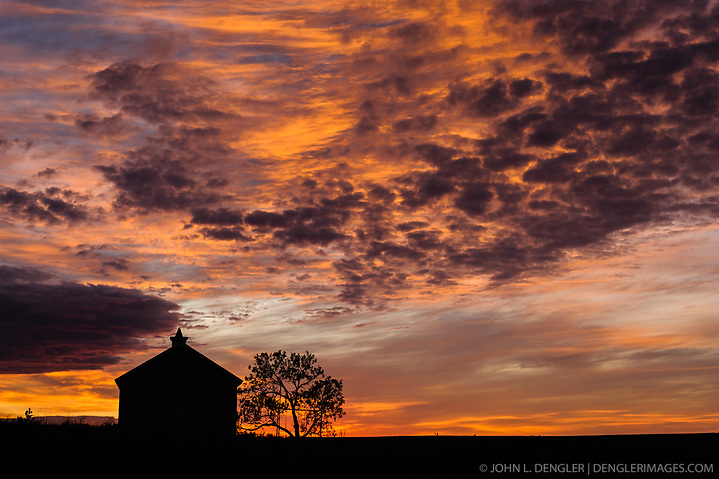 The Lower Fox Creek Schoolhouse and a lone cottonwood tree are silhouetted against a dramatic fall sunrise at the Tallgrass Prairie National Preserve. The 10,894-acre Tallgrass Prairie National Preserve is located in the Flint Hills of Kansas in Chase County near the towns of Strong City and Cottonwood Falls. Less than four percent of the original 140 million acres of tallgrass prairie remains in North America. Most of the remaining tallgrass prairie is in the Flint Hills in Kansas. Tallgrass Prairie National Preserve is the only unit of the National Park Service dedicated to the preservation of the tallgrass prairie ecosystem. The Tallgrass Prairie National Preserve is co-managed with The Nature Conservancy. (John L. Dengler)