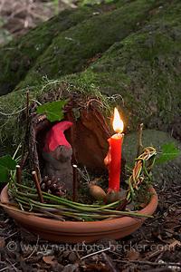 Kinder basteln Zwergengärtchen, Zwergen-Gärtchen aus Naturmaterialien, Bastelei, Tonschale wird mit Moos ausgelegt und mit brennender Kerze, Rinde, Eicheln, Äste und Blätter dekoriert. Zwerg aus Ton. (Frank Hecker)