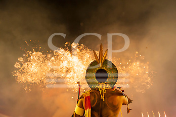 A warrior wearing a green feather cocaa headdress watches the firework display at the International Indigenous Games in Brazil. 24th October 2015 (Sue Cunningham/SCP)