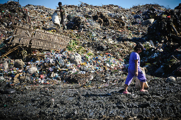 Erni, 10, walking to work at the 'Trash mountain', Makassar, Sulawesi, Indonesia. (Matthew Oldfield)