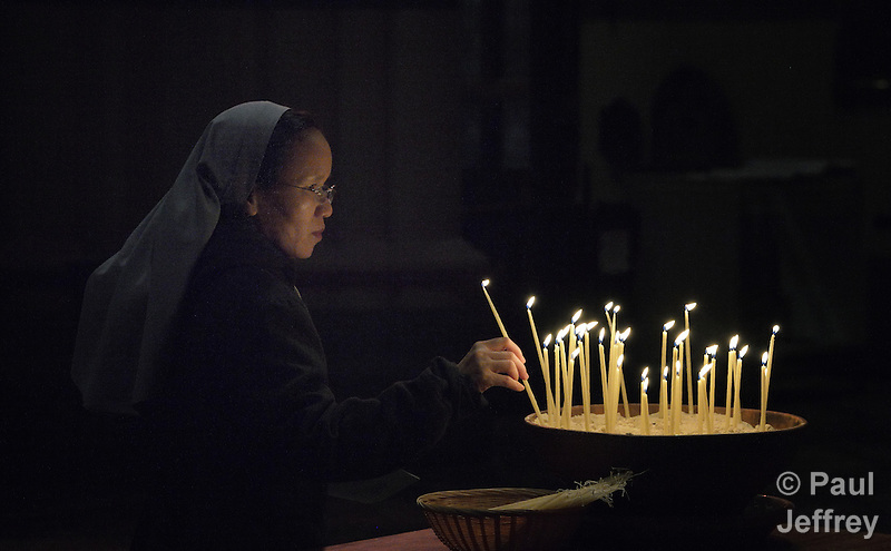 Hien Nguyen, a Catholic nun from Vietnam, lights candles at a July 22, 2014, interfaith service at St. Paul's (Anglican) Cathedral in Melbourne, Australia. The event was a memorial service for those who have died of HIV and AIDS-related causes, and included the involvement of several delegates to the 20th International AIDS Conference. The service came following a march through Melbourne demanding an end to stigma and discrimination against those living with the virus, and a candlelight service in a nearby plaza. (Paul Jeffrey)