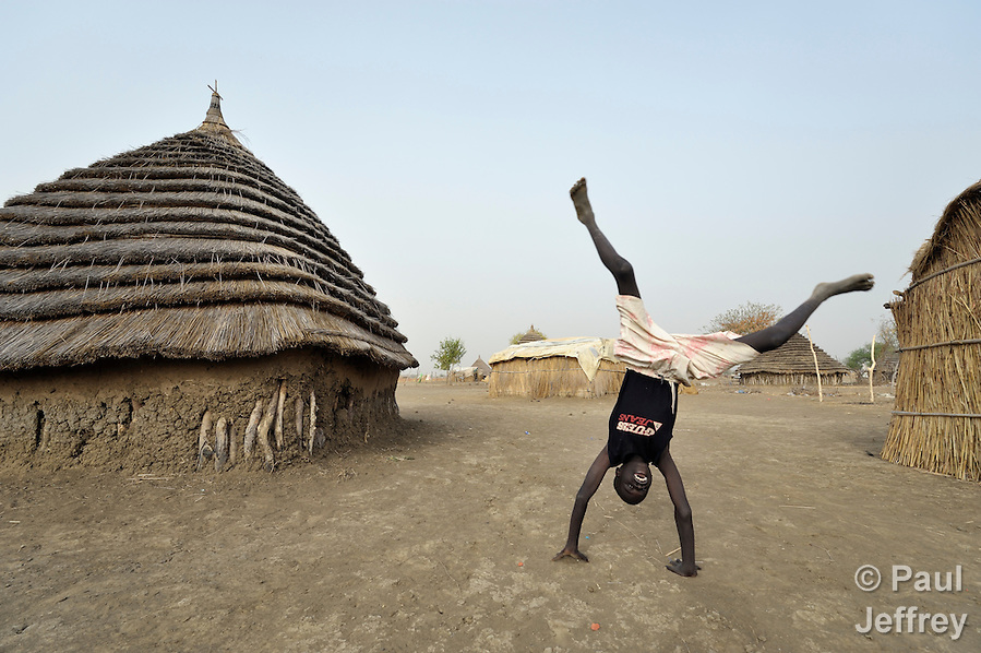 Displaced by war, a boy does a handstand in Agok, a town in the contested Abyei region where tens of thousands of people fled in 2011 after an attack by soldiers and militias from the northern Republic of Sudan on most parts of Abyei. Although the 2005 Comprehensive Peace Agreement called for residents of Abyei--which sits on the border between Sudan and South Sudan--to hold a referendum on whether they wanted to align with the north or the newly independent South Sudan, the government in Khartoum and northern-backed Misseriya nomads, excluded from voting as they only live part of the year in Abyei, blocked the vote and attacked the majority Dinka Ngok population. The African Union has proposed a new peace plan, including a referendum to be held in October 2013, but it has been rejected by the Misseriya and Khartoum. The Catholic parish of Abyei, with support from Caritas South Sudan and other international church partners, has maintained its pastoral presence among the displaced and assisted them with food, shelter, and other relief supplies. (Paul Jeffrey)