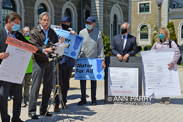 """""""Mineola, NY, USA. April 26, 2021. L-R, DAVE DENENBERG, Co-Director of CAWS; LLOYD NADEL (speaking at mics) attorney for Glen Head-Glenwood Landing Civic Council; ERIC WELTMAN, Senior Organizer for Food & Water Watch and Food & Water Action; (activist); GEORGE POMBAR, Pres. of GH/GL Civic Council; and AGATHA NADEL, Director of NSCC, speak at rally. Faced with a 26% rate increase from New York American Water going into effect May 1, 2021, activists and residents who are NYAW customers rally. (© 2021 Ann Parry/AnnParry.com)"""