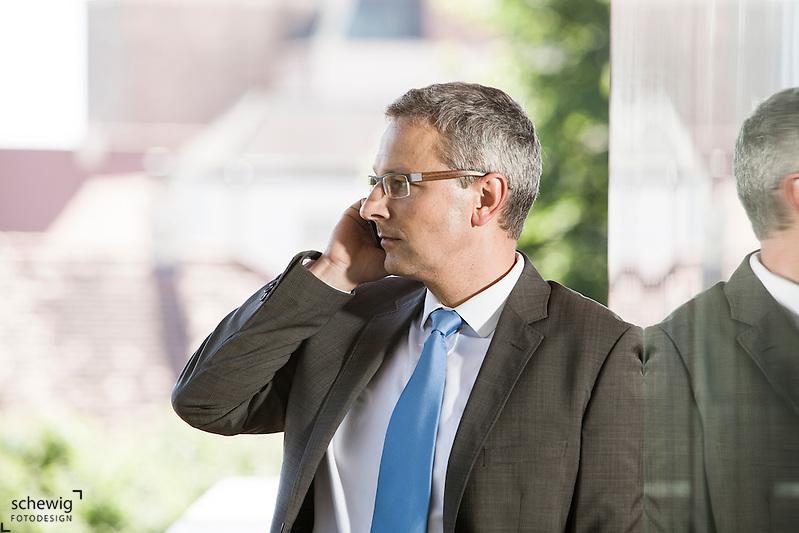 Österreich, Geschäftsmann telefonierend vor Lokal / Büro, Spiegelung (dieter schewig)