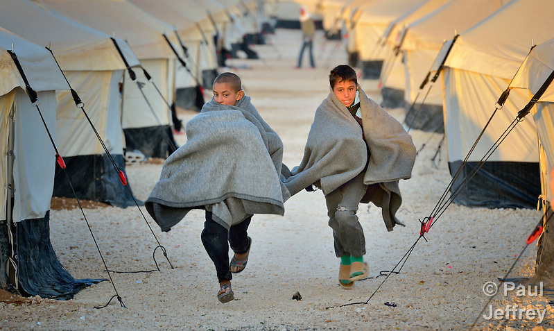 Early in the morning, boys run amid the tents in the Zaatari Refugee Camp, located near Mafraq, Jordan. Opened in July, 2012, the camp holds upwards of 50,000 refugees from the civil war inside Syria, but its numbers are growing. International Orthodox Christian Charities and other members of the ACT Alliance are active in the camp providing essential items and services. (Paul Jeffrey)