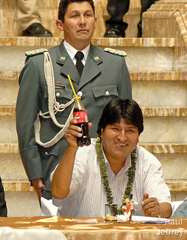 Evo Morales, the first indigenous president of Bolivia. An Aymara, Morales took office in January 2006. Here he salutes a group of students having lunch at the National Palace. He is wearing a necklace of coca leaves and drinking Coca-Cola. (Paul Jeffrey)
