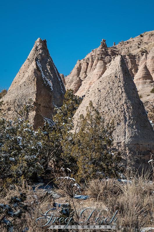 "Kasha-Katuwe Tent Rocks National Monument on the Pajarito Plateau in north-central New Mexico, includes a national recreation trail and ranges from 5,570 feet to 6,760 feet above sea level. It is for foot travel only, and contains two segments that provide opportunities for hiking, birdwatching, geologic observation, and plant identification. The cone-shaped tent rock formations are the products of volcanic eruptions that occurred 6 to 7 million years ago and left pumice, ash, and tuff deposits over 1,000 feet thick. Tremendous explosions from the Jemez volcanic field spewed pyroclasts (rock fragments), while searing hot gases blasted down slopes in an incandescent avalanche called a ""pyroclastic flow."" Precariously perched on many of the tapering hoodoos are boulder caps that protect the softer pumice and tuff below. Some tents have lost their hard, resistant caprocks, and are disintegrating. While fairly uniform in shape, the tent rock formations vary in height from a few feet up to 90 feet. (Greg Disch gdisch@gregdisch.com)"