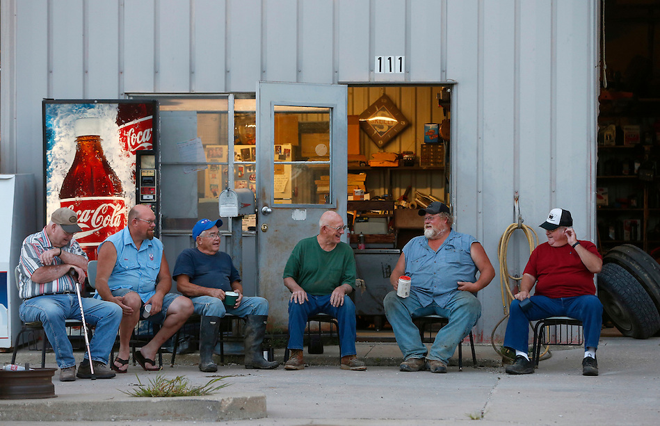 A group of Union County men gather each morning at sunrise outside Frank's Service in Arispe.  From left are Marvin Ringberg, Mike Fry, Don Wilson, Frank Eighme, Randy Needham and Jim Bradley.  They sit on relics of the past, chairs from the long gone Arispe schoolhouse, which closed in 1958. The remote, weathered station is one of the few remaining commercial businesses in the southern Iowa town of about 100. (Christopher Gannon/The Register)