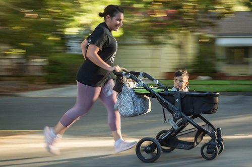 Nursing assistant student Elba Vargas runs with her one year old son, Isaac, on Cedar Street in Calistoga (Clark James Mishler)