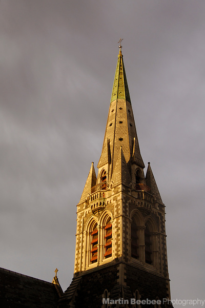 Spire of Christchurch Cathedral lit by morning sun under storm clouds, Christchurch, New Zealand (Martin D. Beebee/Martin Beebee Photography)