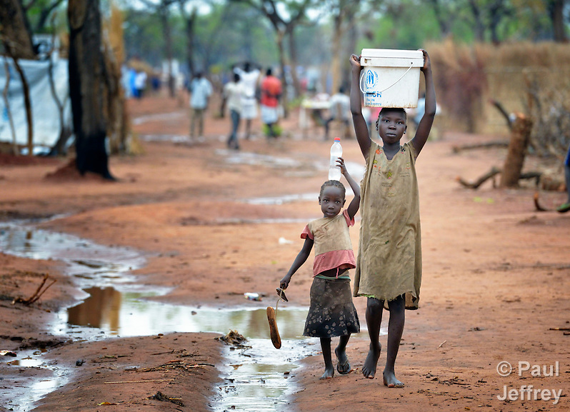 Children carry water in the Ajuong Thok Refugee Camp in South Sudan. The camp, in northern Unity State, hosts thousands of refugees from the Nuba Mountains, located across the nearby border with Sudan. (Paul Jeffrey)