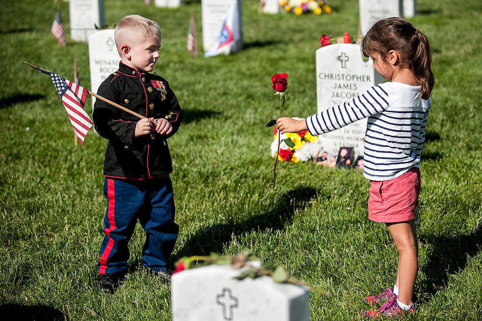 Sophia Namvar, 5, of San Antonio, Texas, offers a rose to Christian Jacobs, 3, of Hertford, North Carolina at Arlington National Cemetery in Arlington, Virginia, USA, on 26 May 2014. Jacobs was visiting the grave of his father, Marine Sgt. Christopher Jacobs, with his mother, Brittany. (PETE MAROVICH/EPA)