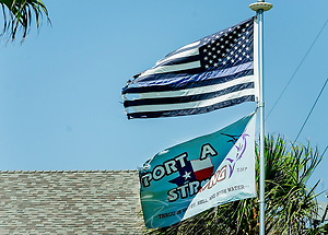 "A ""thin blue line"" flag flies atop a ""Port A Strong"" flag, Aug. 24, 2018, in Port Aransas, Texas. The thin blue line flag, which is an American-style flag with black stripes instead of red and one blue stripe in the middle, is often flown to show support for law enforcement. The ""Port A Strong"" flags can be seen throughout the Texas coastal town, representing the strength and resilience the region showed after being heavily damaged by Hurricane Harvey in 2017. (Photo by Carmen K. Sisson) (Carmen K. Sisson/Cloudybright)"