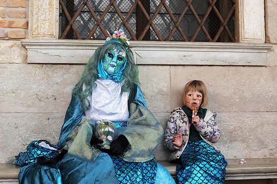 Mother and daughter dressed in traditional mask and costume for Venice Carnival exhausted and sitting on bench at Doge's Palace, girl eating ice cream cone, Piazza San Marco, Venice, Veneto, Italy (Brad Mitchell Photography)