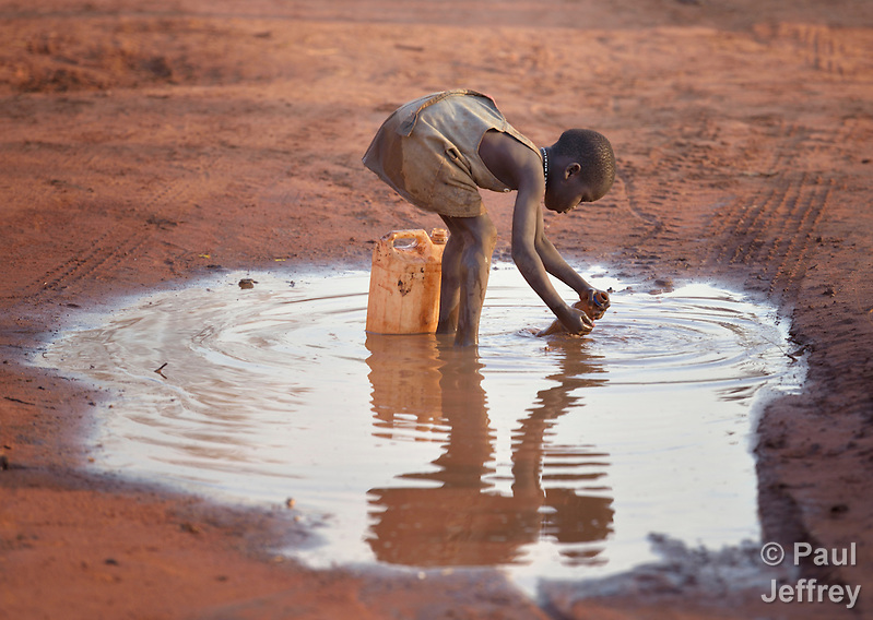 A girl fills a container with muddy water in the Ajuong Thok Refugee Camp in South Sudan. The camp, in northern Unity State, hosts thousands of refugees from the Nuba Mountains, located across the nearby border with Sudan. (Paul Jeffrey)