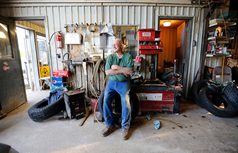 "Frank Eighme, 78, owns Frank's Service in Arispe and still pumps gas, repairs flats and does oil changes daily. ""You gotta have a reason to get out of bed in the morning,"" he says of his passion for the work. (Christopher Gannon/The Register)"