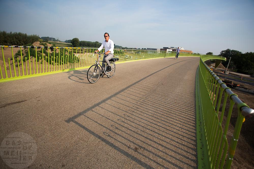 Bij Lent rijden fietsers over 't Groentje, de nieuwe fietsbrug die onderdeel is van het Rijn-Waalpad, de snelfietsroute tussen Arnhem en Nijmegen.