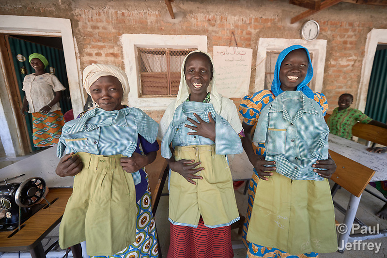 Women proudly display school uniforms they have sewn at the church-run women's center in Gidel, a village in the Nuba Mountains of Sudan. The area is controlled by the Sudan People's Liberation Movement-North, and frequently attacked by the military of Sudan. The Catholic center helps women earn incomes that increase their status in the family and community. (Paul Jeffrey)