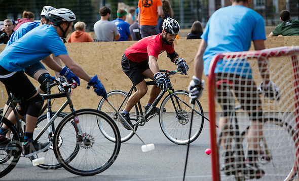 17 AUG 2014 - LONDON, GBR - A player from Mondial (in red and black) looks for a shooting opportunity in his teams game against Sentinels (in blue) at the 2014 London Open Bike Polo tournament in Highbury Fields in London, Great Britain (PHOTO COPYRIGHT © 2014 NIGEL FARROW, ALL RIGHTS RESERVED) (NIGEL FARROW/COPYRIGHT © 2014 NIGEL FARROW : www.nigelfarrow.com)