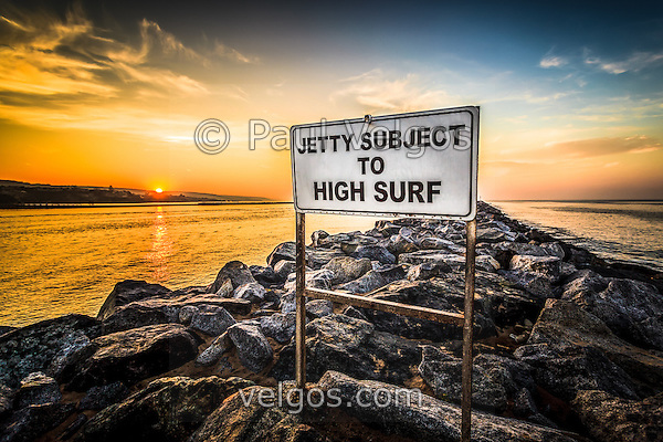 HDR photo of Jetty Subject To High Surf sign at the Newport Beach Jetty and The Wedge. The Jetty is located in Newport Beach California at the end of Balboa Peninsula where Newport Bay meets the Pacific Ocean. Newport Beach is a beach community along the Pacific Ocean in Orange County Southern California. (Photographer: Paul Velgos)