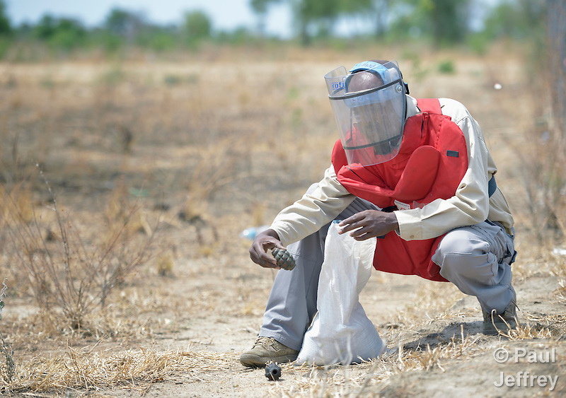Hassan Kossar places hand grenades in a sandbag for transport to a safe disposal site. The grenades were found by an ACT Alliance team as it searched for unexploded ordnance in a civilian area near the South Sudan town of Bor, which has been the scene of heavy fighting between government troops and rebels since a dispute within the ruling party turned violent in December 2013 and quickly ripped the newly independent nation along ethnic and tribal lines. Kossar, from Somaliland, is a senior technical advisor to the explosive ordnance disposal team, part of the humanitarian mine action program of Dan Church Aid, a member of the ACT Alliance. The program also deploys mine risk education teams to help villagers identify and understand the dangers of unexploded ordnance and land mines from this most recent conflict as well as ordnance left over from decades of civil war. (Paul Jeffrey)