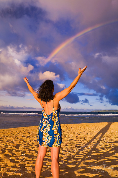 Rainbow over woman raising arms on Tunnels Beach at sunset, Island of Kauai, Hawaii (Russ Bishop/Russ Bishop Photography)