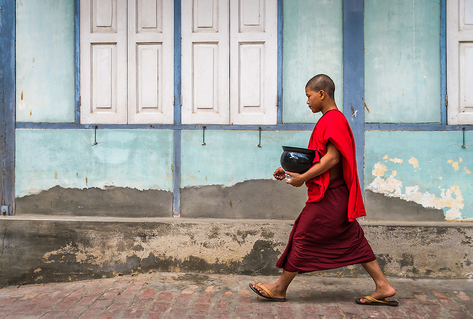 MANDALAY, MYANMAR - CIRCA DECEMBER 2013: Monk walking and carrying bowl with lunch in the Mahar Gandar Yone monastery in Amarpura (Daniel Korzeniewski)