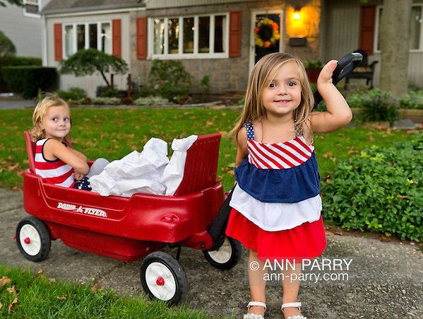 Sept. 11, 2012 - Merrick, New York, U.S. - LYLA W., 3, and KATE O., 2, helping place 500 Luminary Bags (votive candle in each bag will be lit at dark) in front of 215 Wenshaw Park homes, on 11th Anniversary of 9/11, by Wenshaw Park Civic Association (WPCA), Long Island, with over $500 already raised for Twin Towers Orphan Fund. (Ann Parry/-)