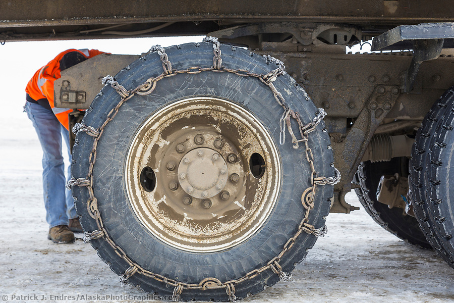 Trucking photos: Truck driver puts chains on the truck tires for better traction crossing the atigun pass of the Brooks Range, Arctic, Alaska. (Patrick J Endres / AlaskaPhotoGraphics.com)
