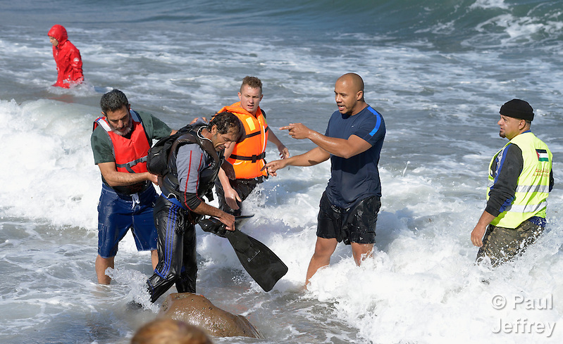 People detain a suspected Turkish migrant smuggler on a beach near Molyvos, on the Greek island of Lesbos on October 31, 2015. He was rescued from the water after volunteers on the island punctured a raft in which he was trying to flee back to Turkey after depositing a load of refugees. He was turned over to the Greek police. (Paul Jeffrey)