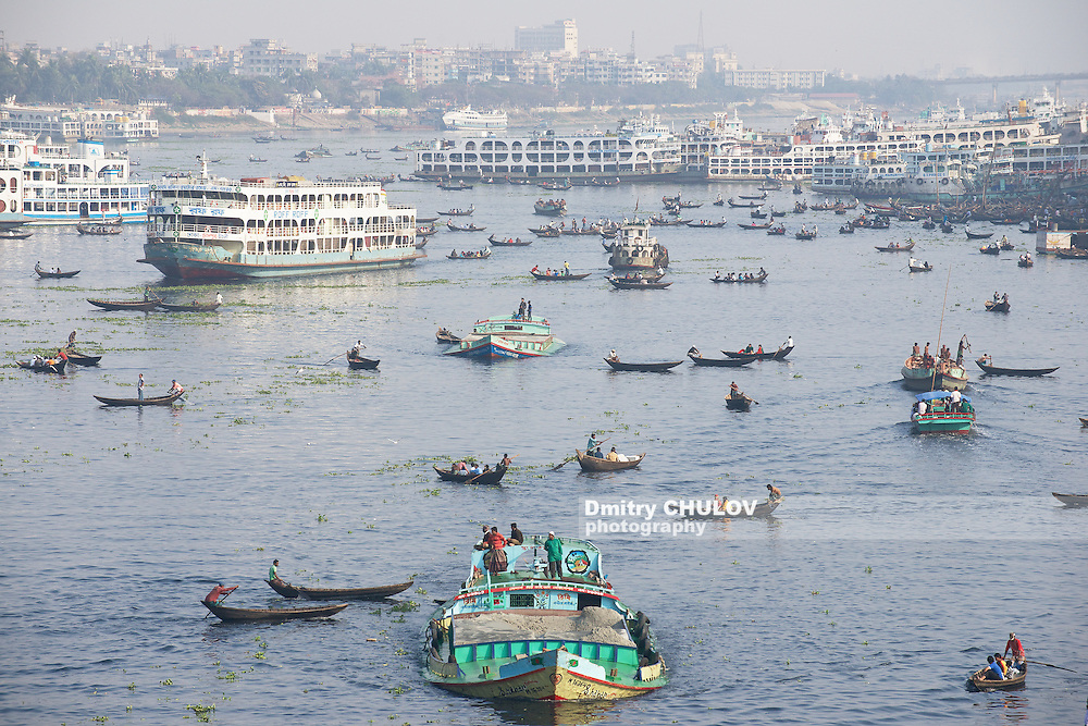 DHAKA, BANGLADESH – FEBRUARY 21: Residents of Dhaka cross Buriganga river by boats in Dhaka, Bangladesh. Thousands of people in one of the most populated capitals of the world use ferry boats daily on the way to work and back home. (Dmitry Chulov)