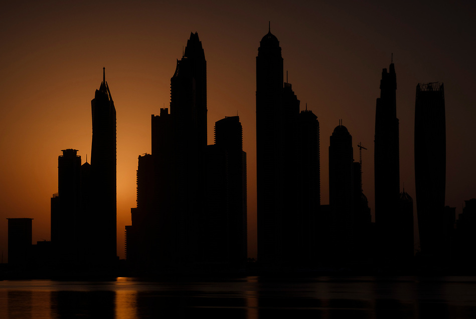UNITED ARAB EMIRATES, DUBAI - CIRCA JANUARY 2017: Silhouette of the Dubai Marina cityscape and skyscrapers as seen from Palm Jumeirah at sunrise. (Daniel Korzeniewski)