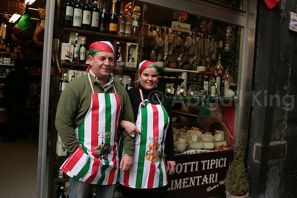 Italy Celebrates 150 Years in Photos - Couple in Italian Flag Aprons Outside Shop