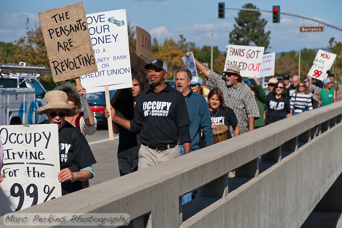 The Occupy Orange County, Irvine march on Saturday November 5 crosses a bridge near the intersection of Barranca and Harvard in Irvine, CA.  Many protesters can be seen holding signs with cars in the background. (Marc C. Perkins)