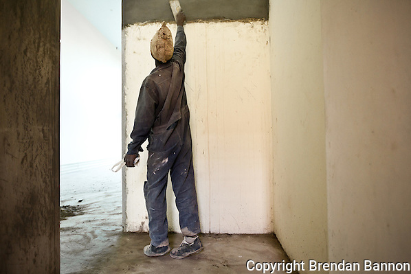 A plasterer at work in Nairobi. He is part of a construction crew working to finish The Greenhouse, a retail and office development. (Brendan Bannon)